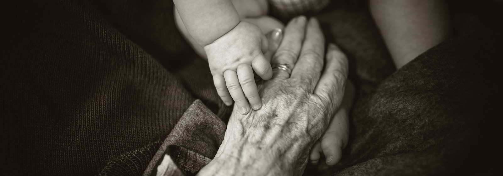 Older person's hand holding the hand and foot of a baby.