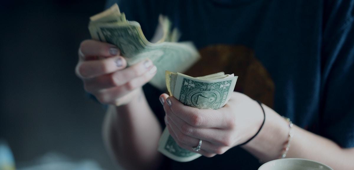 Lady counting dollar bills.