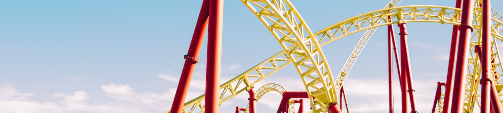 Roller coaster at a theme park with yellow tracks and red supports.