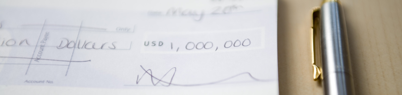 A check for a million dollars next to a nice pen