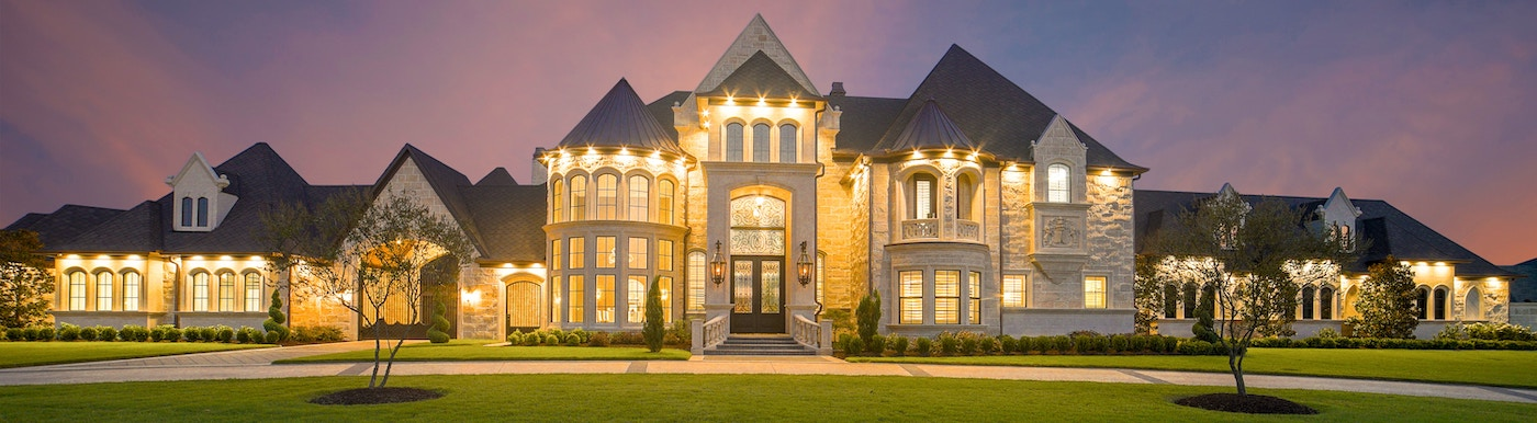 Huge mansion from the front at dusk with lights on
